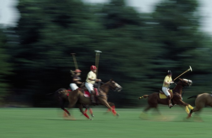 Side profile of three people playing polo